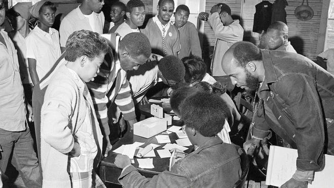 Volunteers stand in line to sign up for the Poor People's Campaign at the Eudora A.M.E. Zion Church in Marks, Mississippi, May 3, 1968. The Rev. James Bevel, SCLC official, bends over at right to check on the applications.