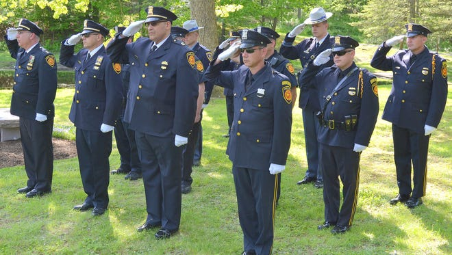 Officers with the Town of Poughkeepsie Police Department salute during a memorial ceremony a Poughkeepsie Rural Cemetery on Friday, May 20, 2016.