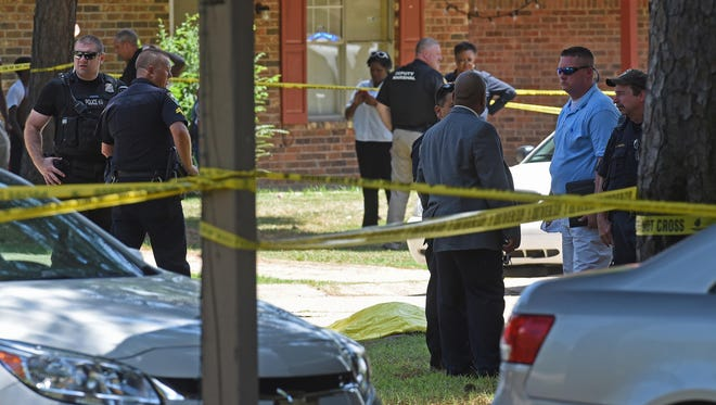 Law enforcement surround the draped body of a deceased man shot late Wednesday morning at the 3300 block of  Bond Drive in Shreveport. A second man was take to University Heath with life threatening injuries. Police have one suspect in custody.