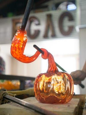 Glass Fellow Devon Murphy adds the stem to a glass pumpkin at First City Art Center.