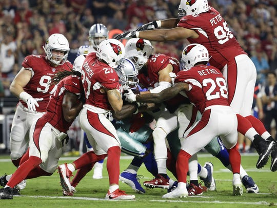 Cowboys wide reciever Dez Bryant pushes a pile of Cardinals