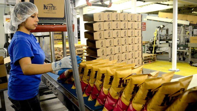 Jemima Onio boxes bags of chips at Kettle Foods in Salem. Diamond Foods Inc., the company that owns Kettle Brand chips, is leasing warehouse space in the former Seneca Cannery building at 1745 Oxford St. SE.