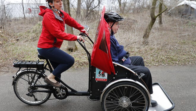 Rikki Profant takes Brewster Village resident Douglas Verhagen on a rickshaw ride last week as part of the Cycling Without Age program.
