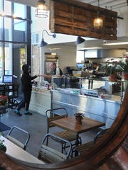 Michael Blackwell, food and beverage manager for Kanaloa Seafood, is reflected in a mirror assisting a customer.