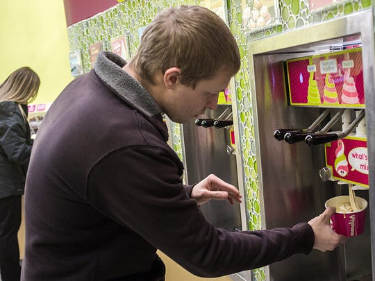 Patrick Roberts from St. Johns fills his cup after sampling various flavors of yogurt at Menchie's Saturday, December 19, 2015.