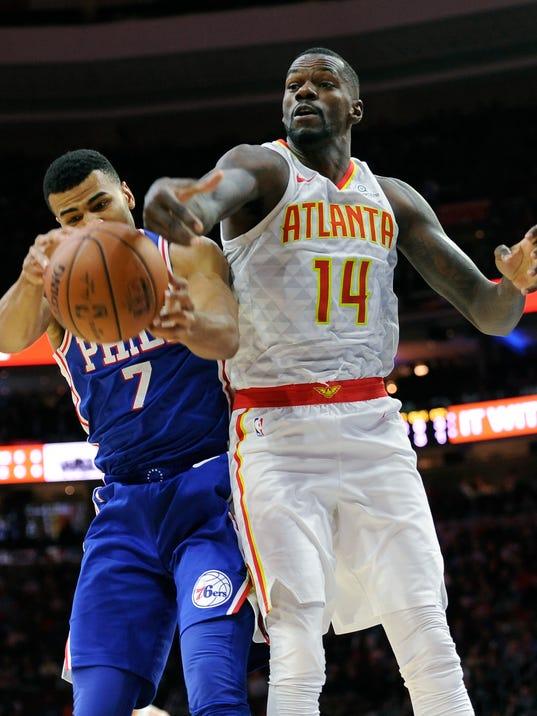 Philadelphia 76ers' Timothe Luwawu-Cabarrot (7) pulls in a rebound over Atlanta Hawks' Dewayne Dedmon during the first half of an NBA basketball game, Wednesday, Nov. 1, 2017, in Philadelphia. (AP Photo/Michael Perez)