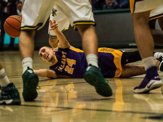 Albany's #24 Joe Cremo hits the floor but manages to