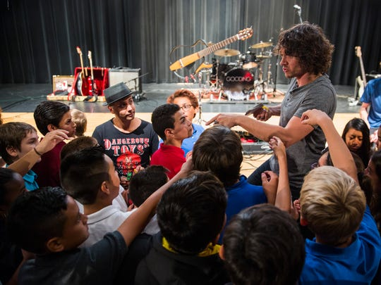 Steven Gooding, lead singer for the band Gooding, hands out copies of his CD to students from Corkscrew Middle School after performing songs about financial literacy at Palmetto Ridge High in Golden Gate Estates on Tuesday, Oct. 18, 2016. The indie rock group performed songs about debt and savings accounts as a part of an outreach program to teach students about the importance of planning for the future.