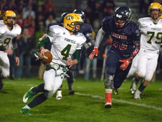 Pennfield quarterback Kollin Kemerling (4) keeps the ball and rushes for positive yards Friday night as the Panthers face off against Lakewood.