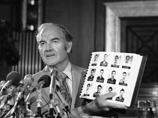 Sen. George McGovern holds up a report from Cuban Prime Minister Fidel Castro on attempts by the Central Intelligence Agency to assassinate him. McGovern made the report public during a Washington news conference July 30, 1975. People pictured on the page were captured conspirators, according to the report.