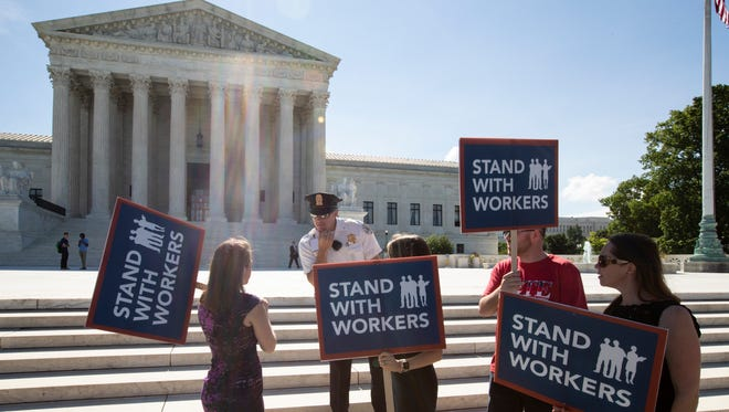 People gather at the Supreme Court awaiting a decision in an Illinois union dues case, Janus vs. AFSCME, in Washington on Monday.