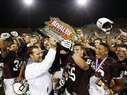 Dowling Catholic head coach Tom Wilson (left) and player Steven Johnson (55) hold up the Great American Rivalry Series trophy Friday, Sept. 18, 2015, after defeating Valley at Drake Stadium in Des Moines.