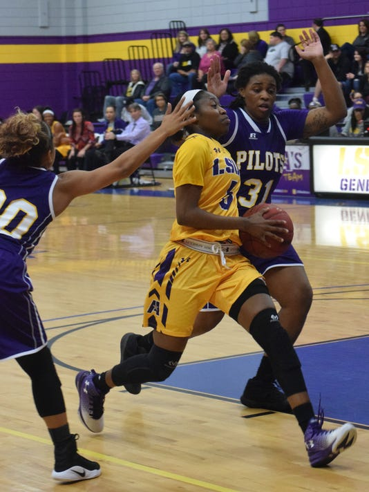 LSUA's Luv Blackburn (5, center) drives to the basket against LSUS's Mikayla Barber (20, left) and Quiana Tucker (31, right).