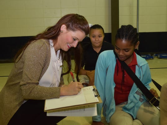 Julius Patrick Elementary School teacher Caitlyn Maddox (left) writes down an educational success that student Leola Stevens told her she accomplished. Julius Patrick students assemble to tell staff members their success stories and they are written on a sticker for the students to wear.