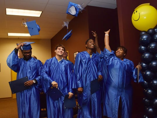 Denerick Byrd (far left), Wildel Miller, Raymond Green and Kanina White throw their hats in the air after graduating from the GEO Reentry Services Winter 2015 Transition Celebration held Thursday.