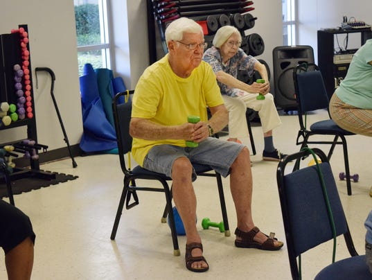 """Russ Marsh, 79, works out with dumb bells during a Chair Aerobics class at the Turner Street YWCA. Marsh's wife Irene also attends the class. """"I have bad back stenosis,"""" he said. Chair Aerobics, he says, helps him out. He also works out in the gym."""