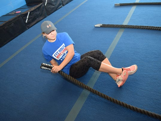 Tobi Soileau, general manager of Alexandria Fit Body Boot Camp, performs Russian twists using battle ropes. The battle ropes can be used to work on the upper body, arms, legs and core depending on the exercise.