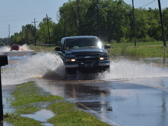 Vehicles drive through receding waters on McKeithen Drive Monday afternoon.