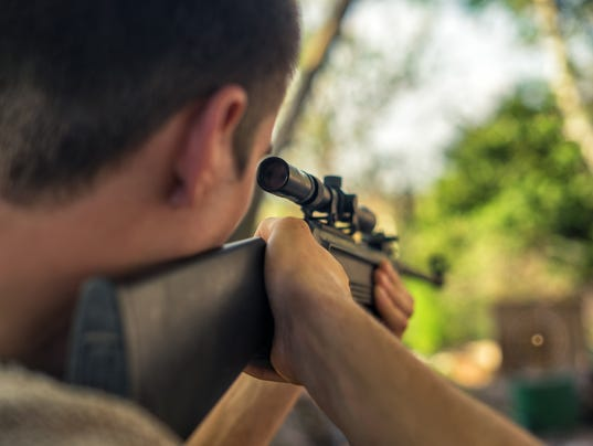 The man takes aim at the target with a sniper rifle. Selective Focus