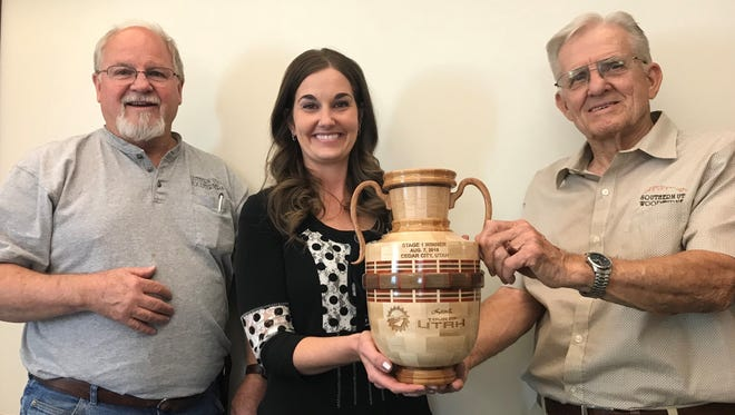 Southern Utah Wood Turners Club President Will Arcularius (left) and vase trophy maker Jack Gunn present this hand-crafted wooden trophy to Mayor Maile Wilson-Edwards on June 20, 2018. The mayor will bestow this community gift to the Tour of Utah Stage 1 winner on Aug. 7, 2018.