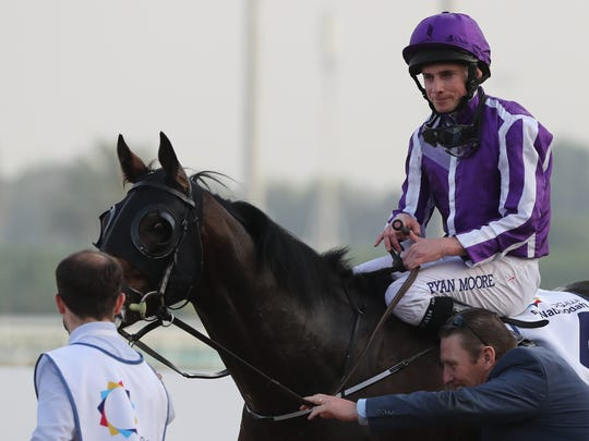 Jockey Ryan Moore gestures as he rides Mendelssohn after winning the UAE Derby horse race at the Dubai World Cup in the Meydan Racecourse on March 31, 2018 in Dubai.