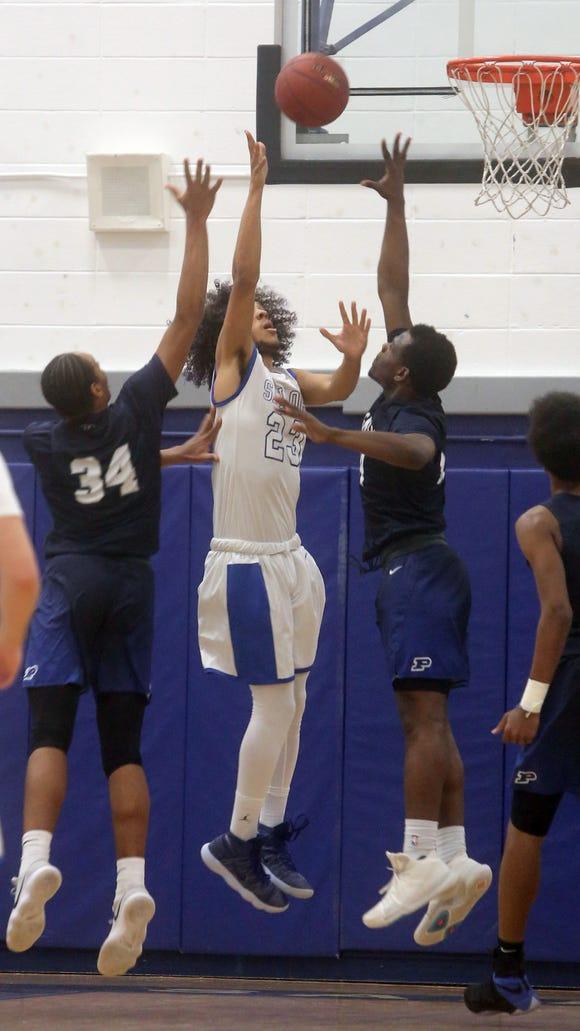 Kyle James of Hendrick Hudson shoots while being defended by Poughkeepsie's Davontrey Thomas and Tremell Reaves during a varsity basketball game at Hendrick Hudson High School Feb. 6, 2018. Hendrick Hudson defeated Poughkeepsie 54-51.
