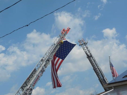 Ladder trucks from Millville Fire Department raised