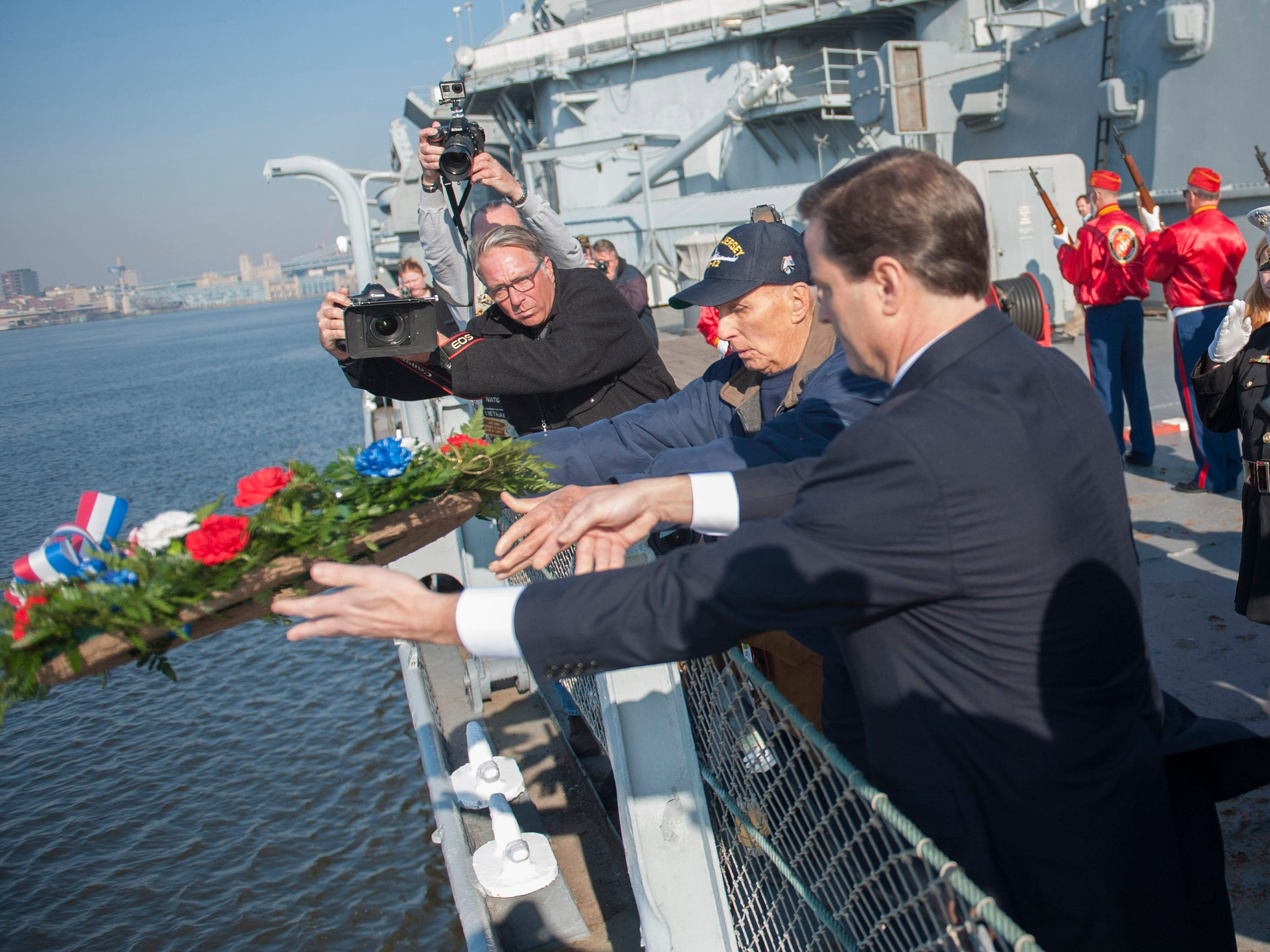 Congressman Donald Norcross and WWII Veteran Russell Collins of Palmyra toss the Memorial Wreath in the Delaware River during the Pearl Harbor Day Commemoration aboard the Battleship New Jersey. Monday, December 7, 2015.