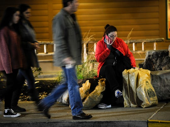 Beth Edwards waits for her friend to finish shopping outside Bass Pro Shop at Opry Mills Mall early morning Friday, Nov. 25, 2016.