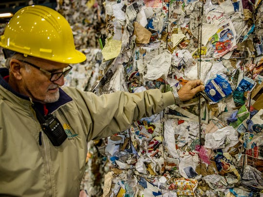 Gil Valente inspects some recycling materials. Interestingly, the composition of recyclables has changed throughout the years, with a major shift away from newsprint to cardboard.