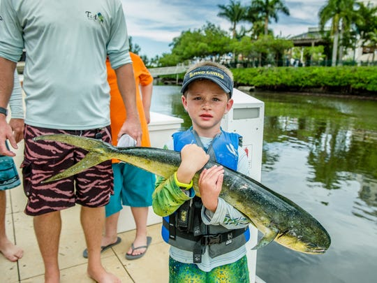 Shaffer Okell, age 6, holds his dolphin weighing in at 8.8 lbs.