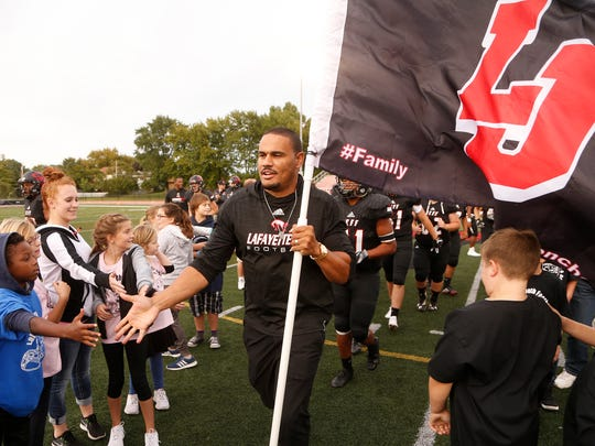 Former Lafayette Jeff, Purdue and NFL veteran Dustin Keller slaps hands with youngsters after leading the Bronchos onto the field to face McCutcheon Friday, September 1, 2017, at Scheumann Stadium. Jeff defeated McCutcheon 28-10.