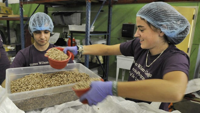 Warren Wilson College students fill bags with pinto beans at MANNA Food Bank.