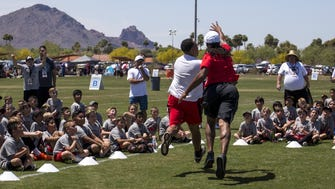 Arizona Republic sports columnist Greg Moore takes on Cardinals wide receiver Larry Fitzgerald at the closing ceremony of the youth football camp in Fitzgerald's name, at Salt River Fields on Saturday, April 21, 2018. Johanna Huckeba/azcentral