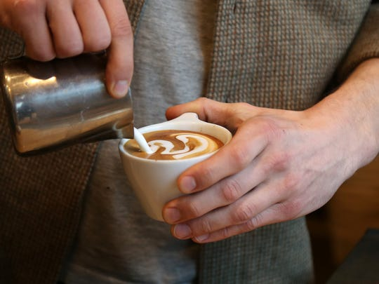 Detail photo of a barista pouring over at Collective