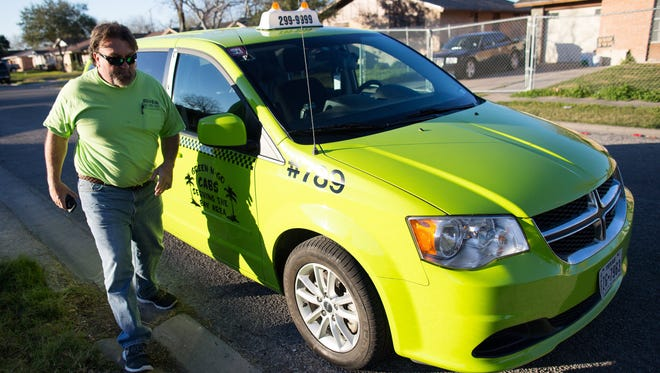 Green-N-Go Cab driver Phillip Benesh walks to the front of his cab after helping a fare into the back, Thursday, Feb. 4, 2016.