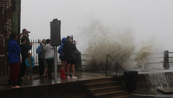 People watch a wave crash over a sea wall in Charleston on Monday.