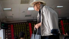 A man leaves as stock investors monitor the stock prices