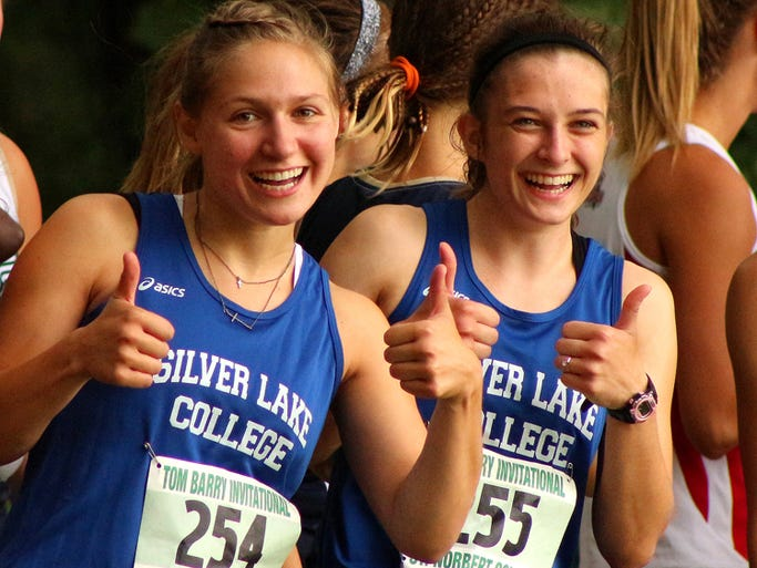 Silver Lake College cross country runners Abby Rieth, left, of Chilton, Wis., and Taylor VandenPlas of New Franken, Wis., show their enthusiasm before the start of the Tom Barry Invitational on Aug. 30, 2014, in Green Bay. Photo by Benjamin Wideman / Silver Lake College Director of Communications and Sports Information