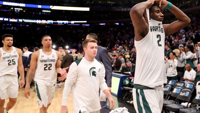 MSU's Jaren Jackson Jr., right, and Miles Bridges, back, leave the court after the Spartans' 75-64 loss to Michigan on Saturday.