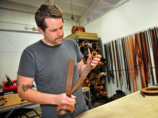 Emil Congdon, owner of Emil Erwin, works in his new studio in the Buchanan Street area. The high-end leather goods maker has set up shop on Buchanan after moving from mixed-use Marathon Village on Clinton Street near downtown.