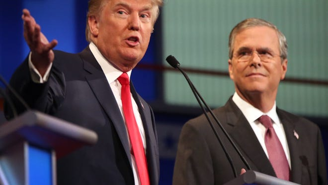 Republican presidential candidate Donald Trump speaks as Jeb Bush listens during the first Republican presidential debate at the Quicken Loans Arena Thursday, Aug. 6, 2015, in Cleveland. (AP Photo/Andrew Harnik)