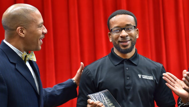 Jackson Public School Superintendent Cedrick Gray congratulates William Herring, JPS Parent of the Year 2015, during a ceremony Monday at Spann Elementary School.