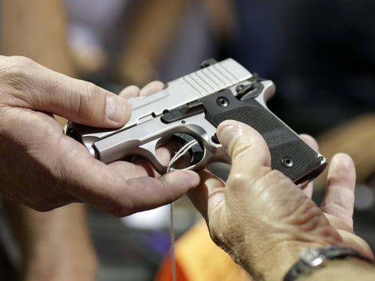 A customer handles a pistol at a Florida gun show in 2016.