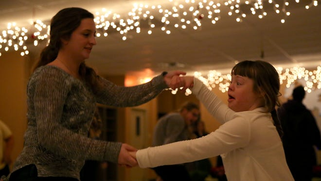 Kenzie Gardner and Adena Anderson dance together during a winter dance for special needs kids at the Southside Rec Center on Friday night.