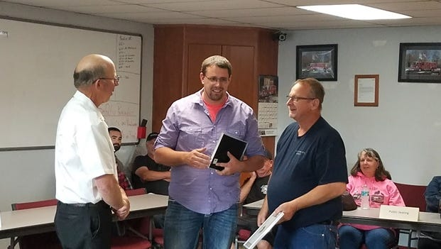 Aumsville Rural Fire District Chief Roy Hari presents city residents Steve Ellis and Ryan Woodward with the Emergency Action Award.