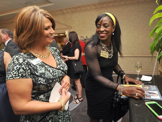 Olympian Ruthie Bolton (right) signs a program for Tandy Haley during a reception Friday before the Mississippi Sports Hall of Fame and Museum induction ceremony at the Hilton on County Line Road in Jackson.