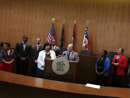 Detroit Mayor Mike Duggan stands with Detroit City Council before Detroit emergency manager Kevyn Orr signs Order #42 that gives all authority back to the mayor and City Council.