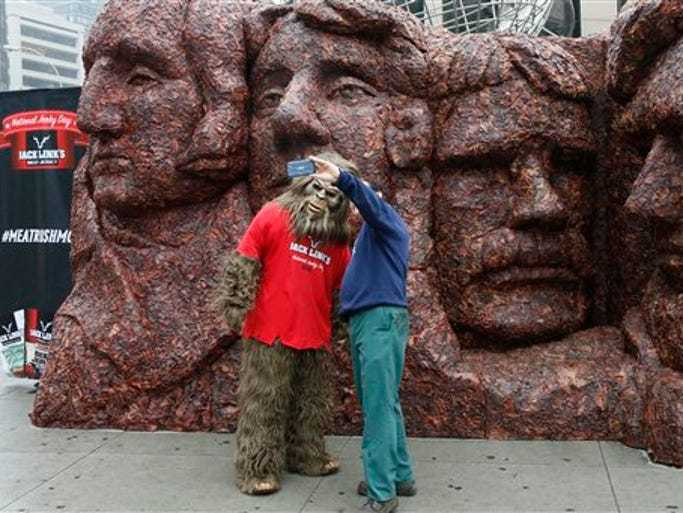 IMAGE DISTRIBUTED FOR JACK'S LINKS - Sasquatch poses with a fan in front of Meat Rushmore, a 13-foot tall, 17-foot wide meat replica of Mount Rushmore National Memorial, on Thursday, June 12, 2014, in New York City's Columbus Circle. The structure, created from more than 1,600 pounds of Jack Link's protein-packed beef, pork and turkey jerky, was created to celebrate the third annual National Jerky Day. (Photo by Stuart Ramson/Invision for Jack Link's/AP Images)