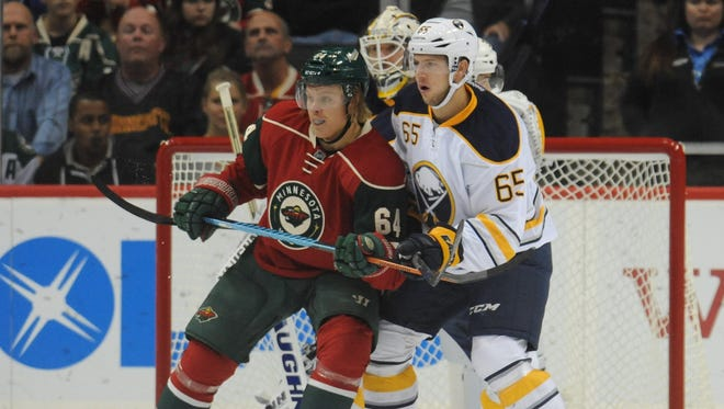 Matt Donovan works to move Mikael Granlund of the Minnesota Wild out of the deep slot during a preseason game with the Buffalo Sabres on Oct. 1.